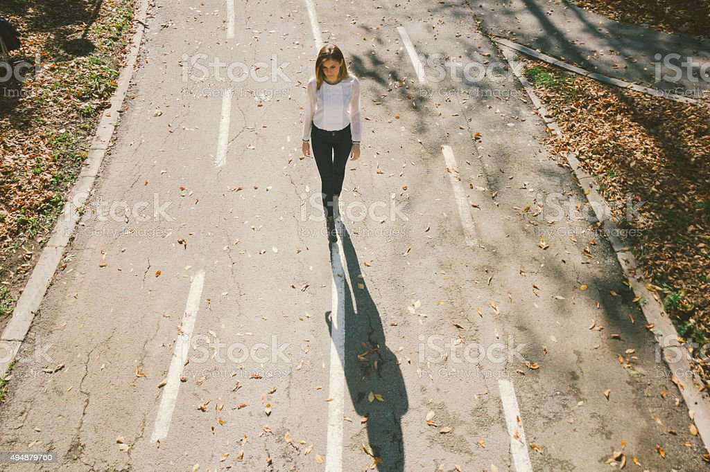 Cute lonely girl walking down the street in autumn stock photo
