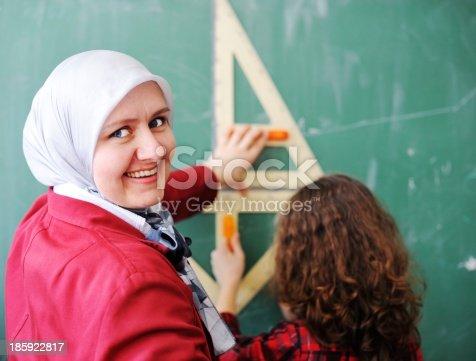 157687202 istock photo Cute lovely school children at classroom having education activi 185922817