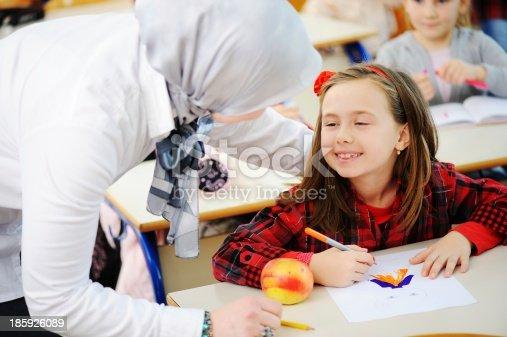 157687202 istock photo Cute lovely school children at classroom having education activi 185926089