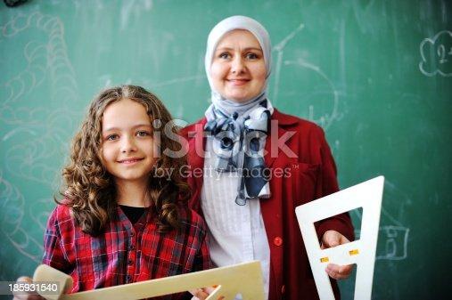 157687202 istock photo Cute lovely school children at classroom having education activi 185931540