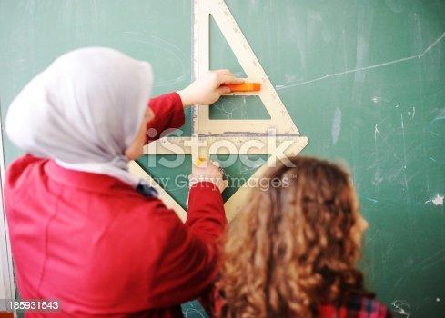 157687202 istock photo Cute lovely school children at classroom having education activi 185931543