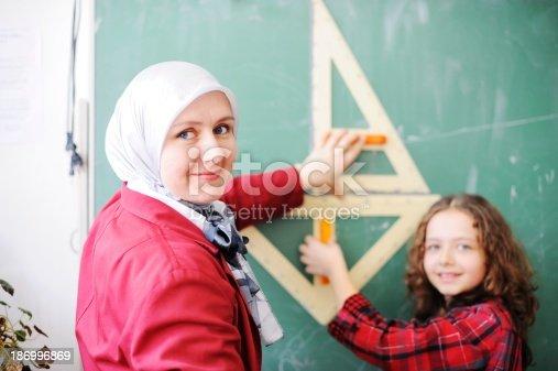 157687202 istock photo Cute lovely school children at classroom having education activi 186996869