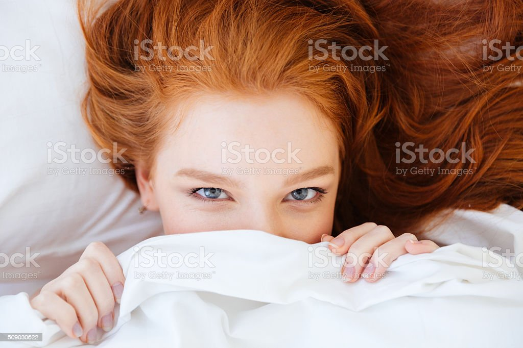 Cute lovely woman with red hair hiding under white blanket stock photo