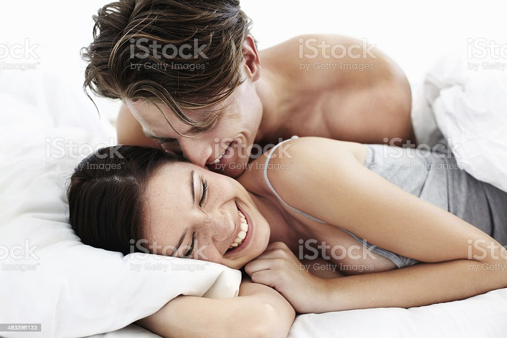 Cute loving couple smiling in bed stock photo
