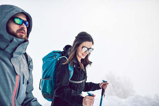 Cute Male And Female Alpinists Having A Conversation While Tackling Mist And Snow
