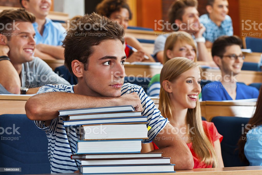 Cute male student Large group of happy high school students sitting in the lecture hall. Focus on the pensive young man with piled up books, looking away. 20-24 Years Stock Photo
