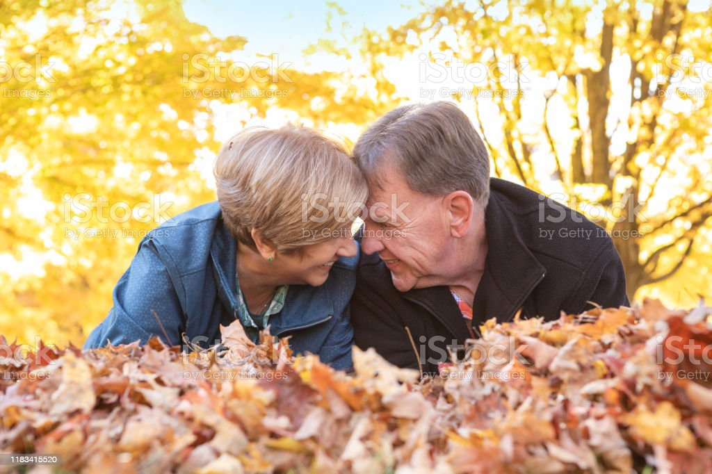 Cute Mature Couple Face to Face in Fall Leaves A cute mature couple in their 60s with their heads together and they lay in the fall leaves. 65-69 Years Stock Photo