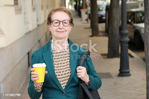 Cute mature woman holding coffee cup outdoors.