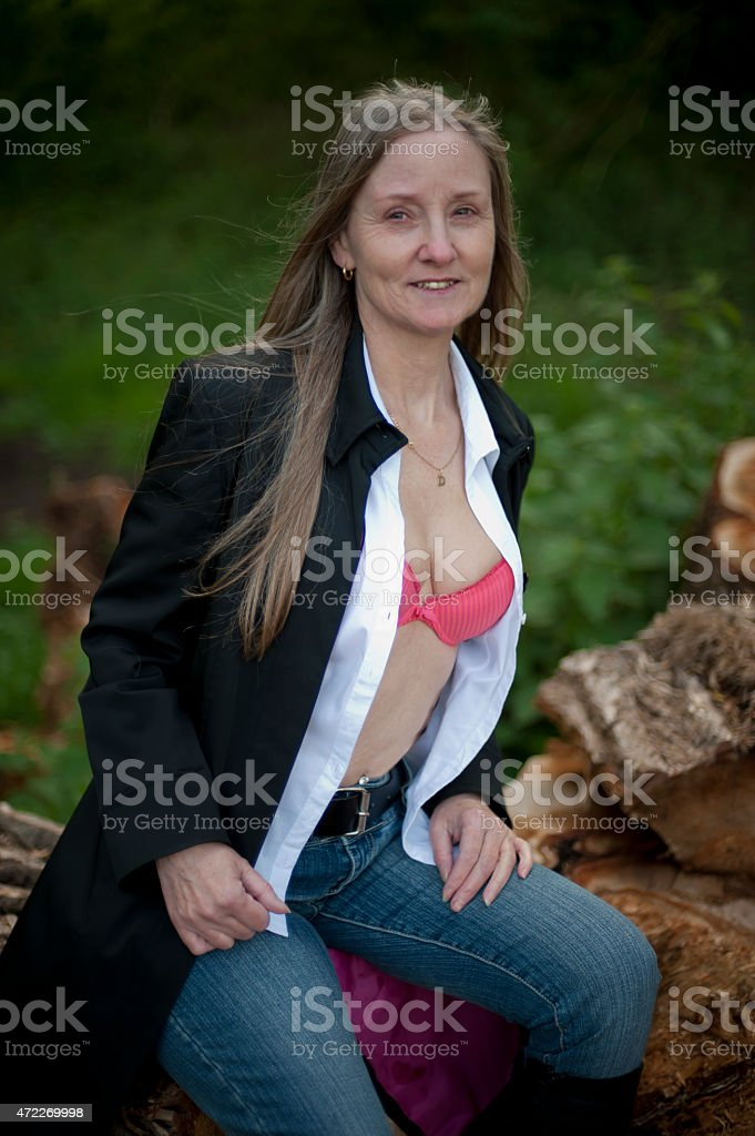 cute mature woman posing in forest on a spring afternoon stock photo