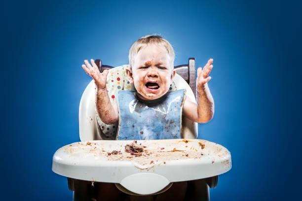 Bebê fofo desarrumado, coberto de comida - foto de acervo