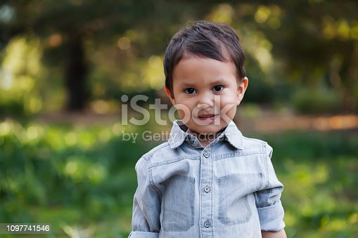 A cute mexican boy standing in a green wooded field, with gentle smile on his face and wearing a long sleeve shirt.