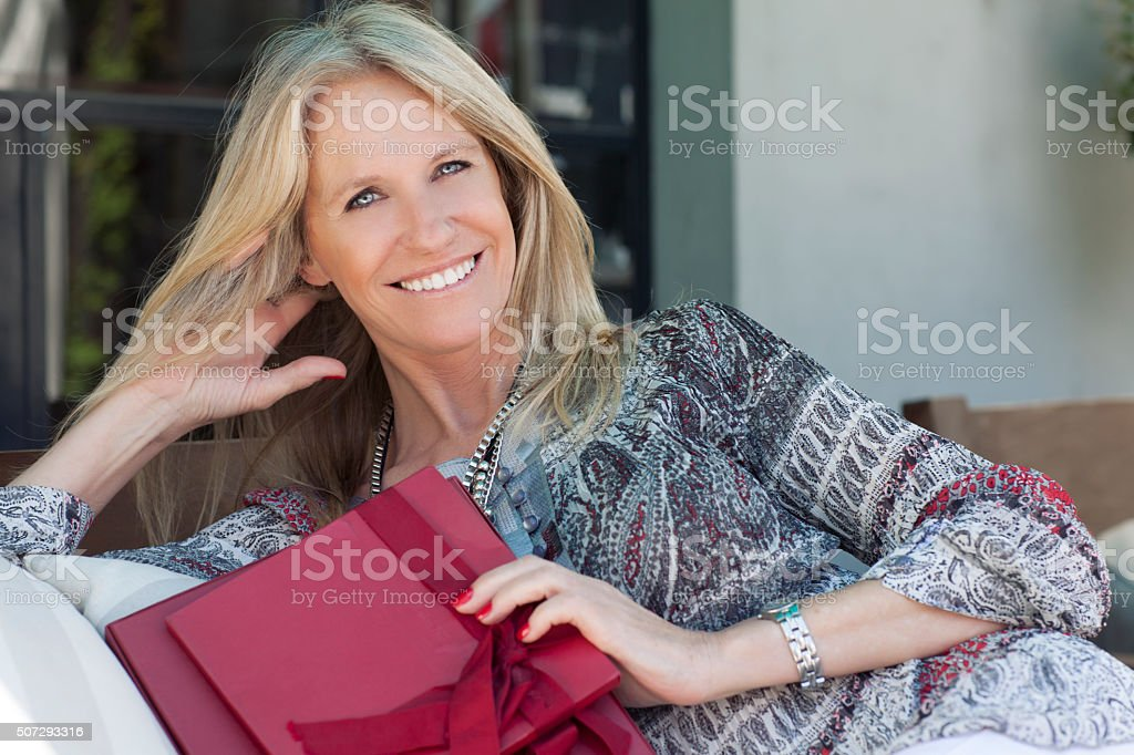 Cute middle age woman with gift at home in outdoors stock photo