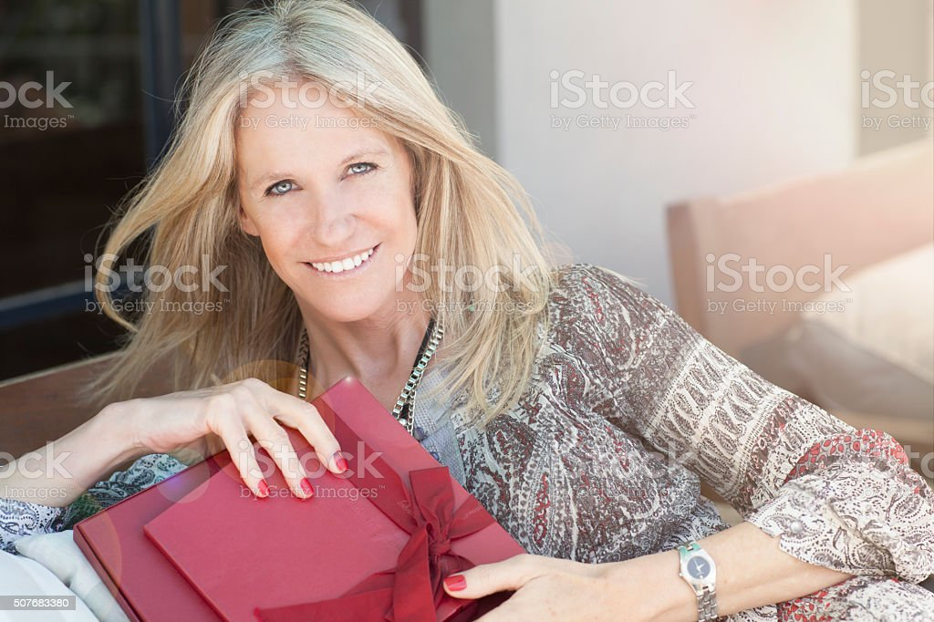 Cute middle age woman with gift in outdoors stock photo