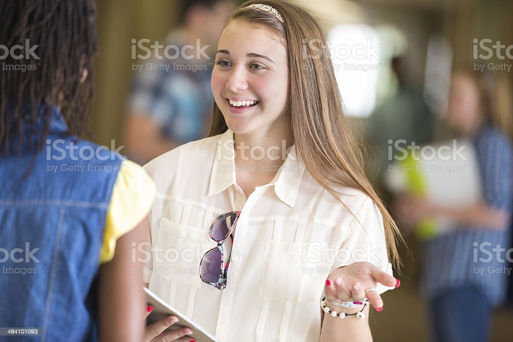 Cute Middle School Student Talking To Friend In Hallway Stock Photo