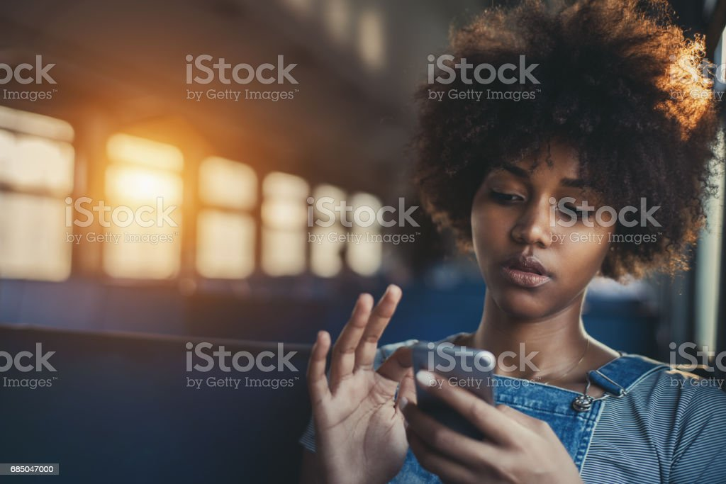 Cute mixed girl in train chatting via smartphone - Royalty-free African Ethnicity Stock Photo