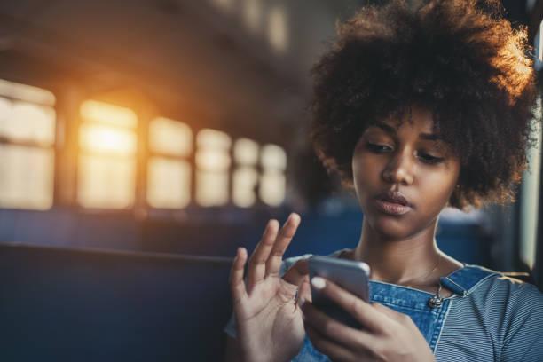 Cute mixed girl in train chatting via smartphone stock photo