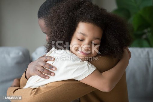 Cute funny mixed race child daughter embracing black father holding tight feeling love connection affection concept, happy african family dad and little kid girl hugging cuddling bonding at home
