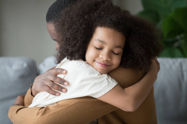 Cute mixed race child daughter embracing father feeling love connection stock photo