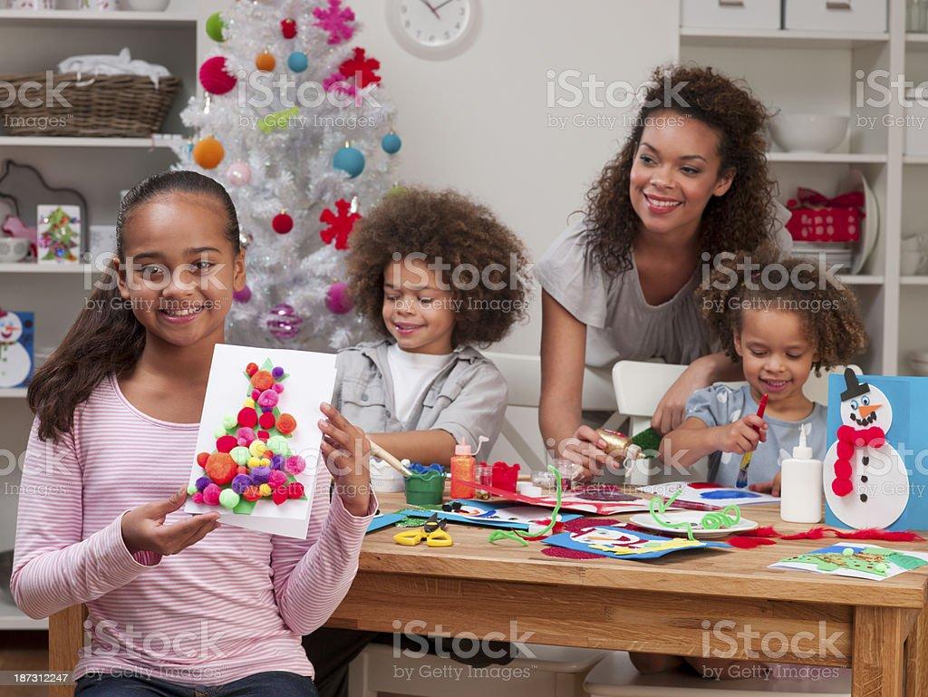 Cute mixed race girl holding handmade Christmas cards royalty-free stock photo