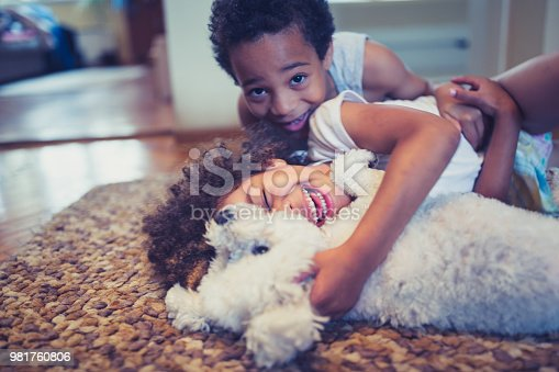 Cute, mixed race siblings, having fun playing with their dog, bichon frise indoors in living room