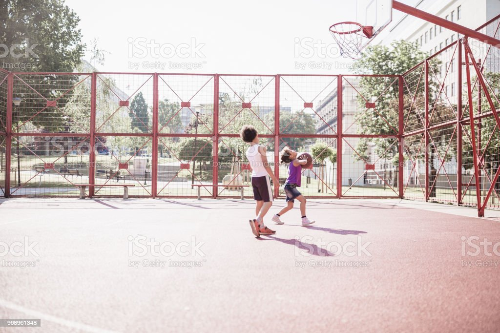 Cute mixed race siblings playing basketball outdoors on basketball court stock photo