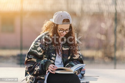 521911045istockphoto Cute mixed race teenage girl with curly hear dressed in military jacket sitting outdoors and reading book. 1132949135