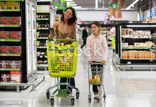 Cute mother and daughter each pushing their shopping cart while taking a selfie with smartphone smiling at the supermarket - Lifestyles