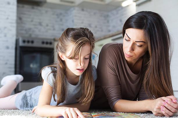 cute mother and daughter reading book - haushaltsbuch führen stock-fotos und bilder