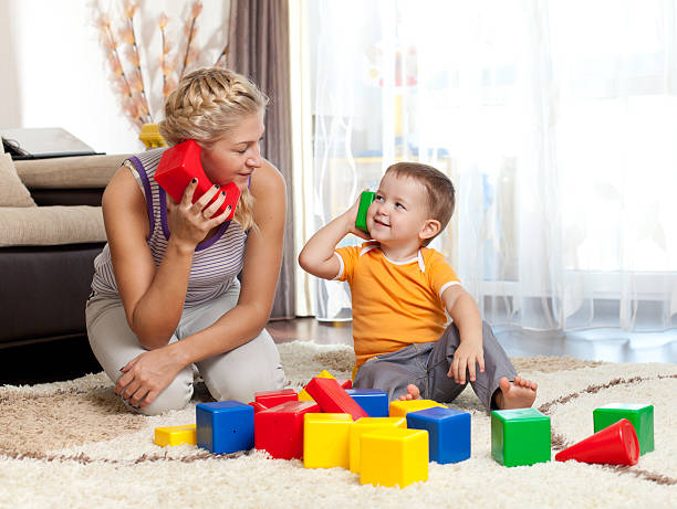 cute mother and kid boy playing together indoor stock photo