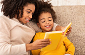 Cute Black Mother And Little Daughter Reading Book Together Sitting On Couch At Home. Bedtime Story Concept