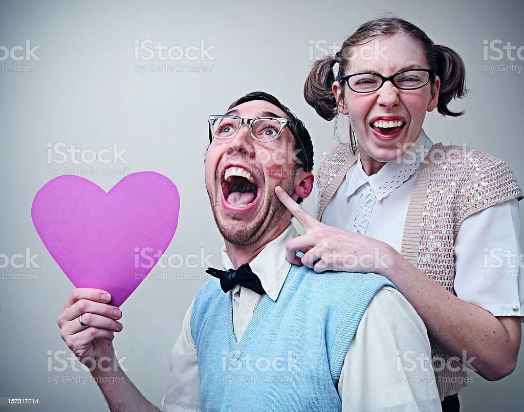 Cute Nerd Guy and Girl in Love Holding A Heart royalty-free stock photo