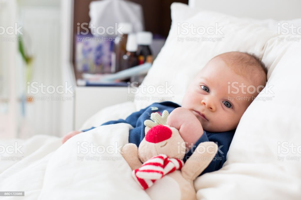 Cute newborn baby boy, lying in bed with cold stock photo