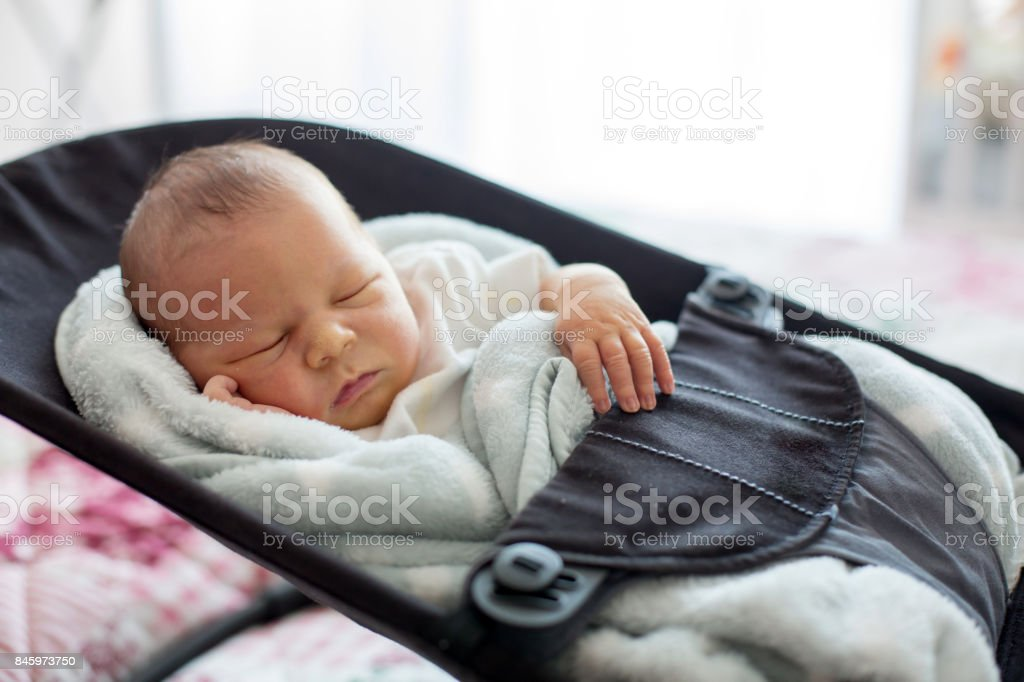 Cute newborn baby boy, sleeping in a swing stock photo