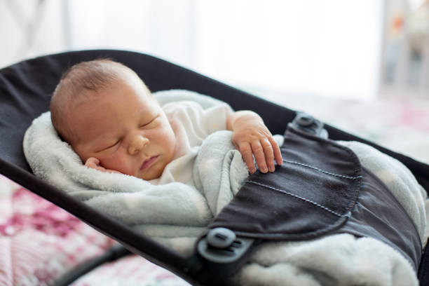 Cute newborn baby boy, sleeping in a swing Cute newborn baby boy, sleeping in a swing, covered with blanket, casual clothing alternative pose stock pictures, royalty-free photos & images
