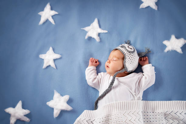 Cute newborn baby girl lying in the bed. 2 month old child in owl hat sleeping on blue blanket stock photo