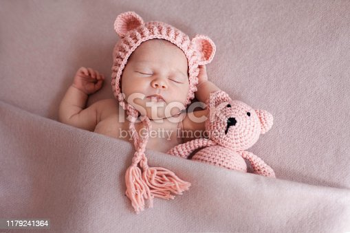 Portrait of cute newborn baby girl wearing pink hat with ears and sleeping with knitted teddy bear under pink blanket. Horizontal Image.