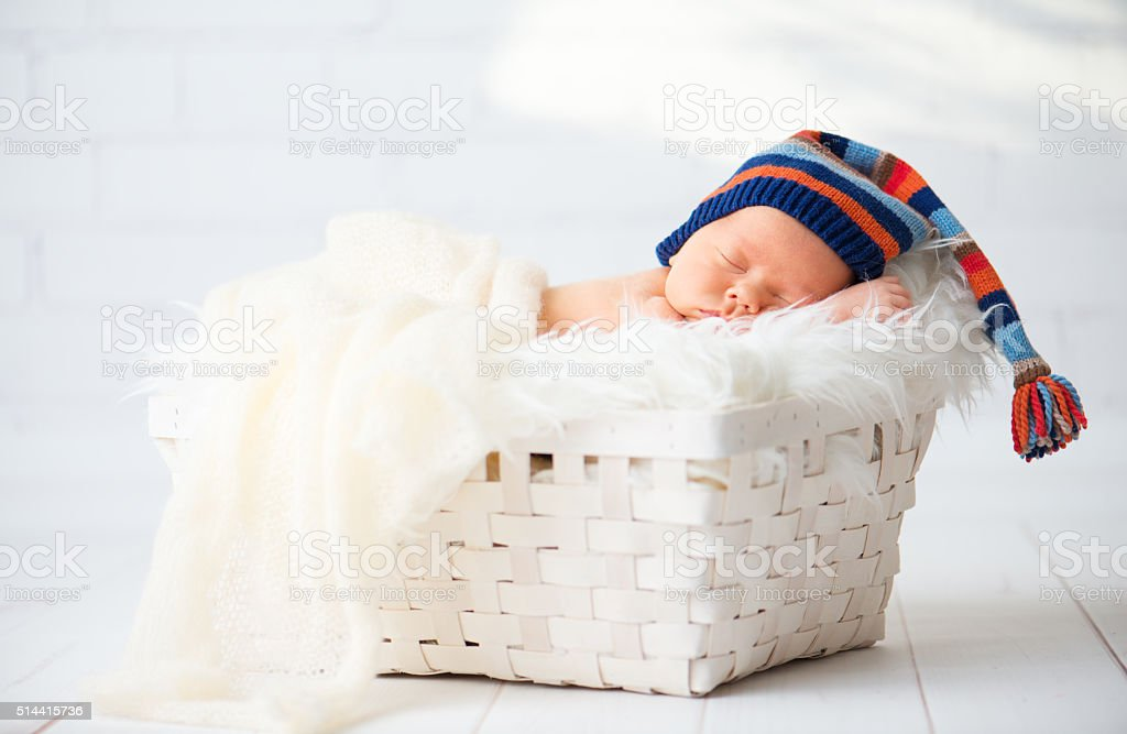 dcde79451cd Cute newborn baby in blue knit cap sleeping in basket royalty-free stock  photo