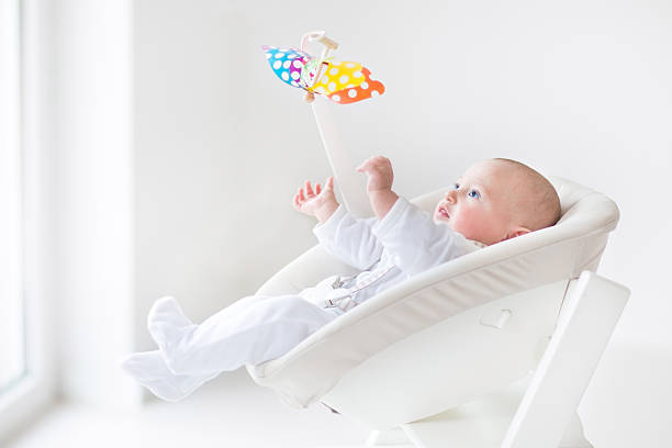 lindo bebê recém-nascido observação de brinquedo colorido em branco móvel, cadeira - mobile - fotografias e filmes do acervo