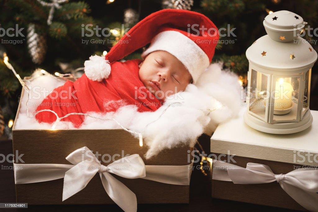 Süßes Neugeborenes Baby trägt Weihnachtsmann Hut schläft in der Weihnachts-Geschenk-Box - Lizenzfrei Augen geschlossen Stock-Foto