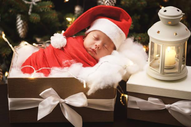 schattige pasgeboren baby dragen van santa claus hoed is slapen in de doos van de gift van kerstmis - pinaceae stockfoto's en -beelden