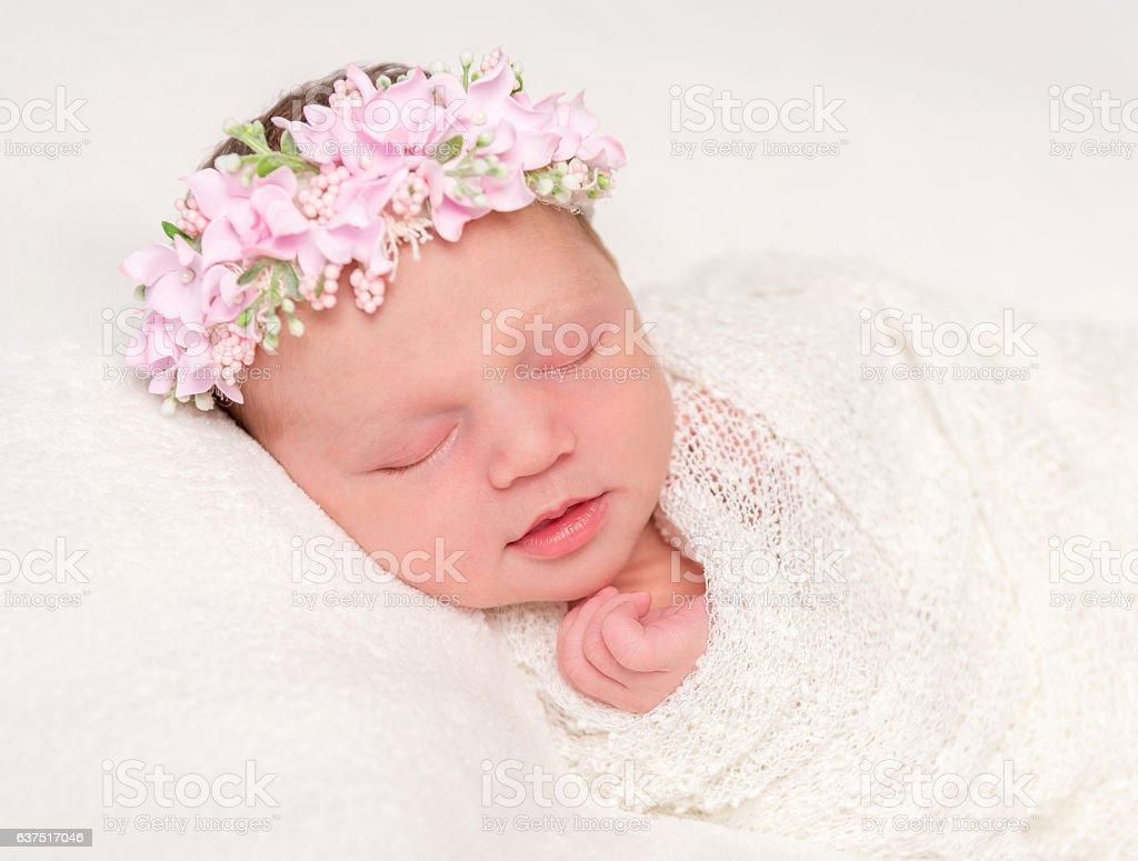 cute newborn in headband with flowers smiling asleep stock photo