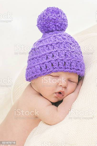 Photo of Cute newborn in knitted hat is sleeping