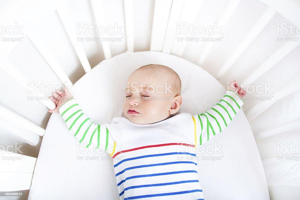 Cute newborn little boy sleeping in a white round crib stock photo