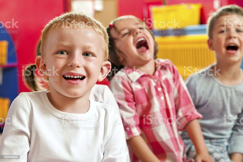 Cute Nursery School Children A happy children sitting in a playroom in a nursery school and laughing. 4-5 Years Stock Photo