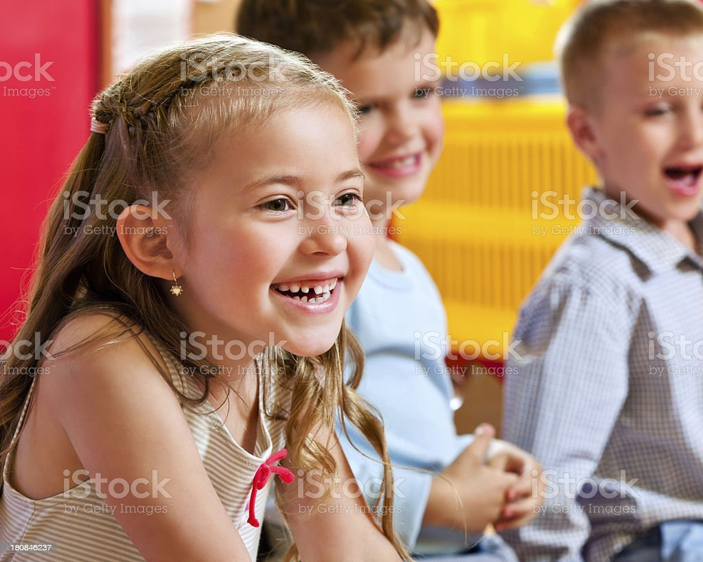 Cute Nursery School Children Focus on the cute little girl sitting in a playroom with her friends in the background and laughing. 4-5 Years Stock Photo