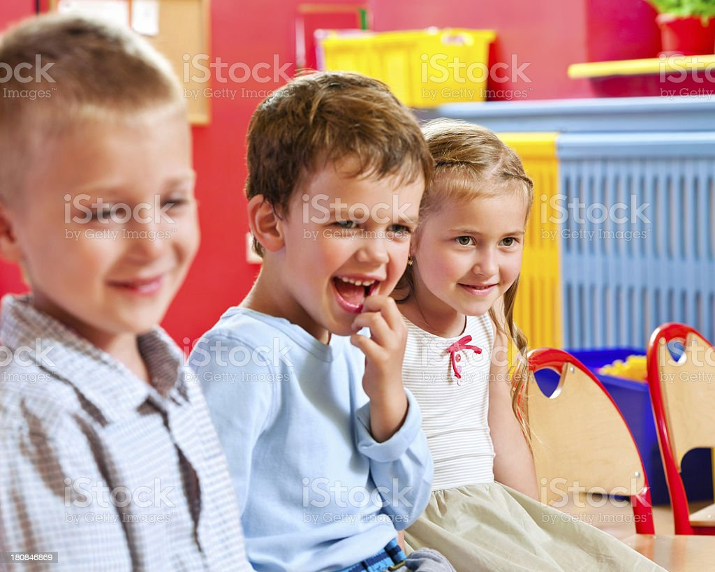 Cute Nursery School Children A happy children sitting in a playroom in a nursery school and smiling. 4-5 Years Stock Photo