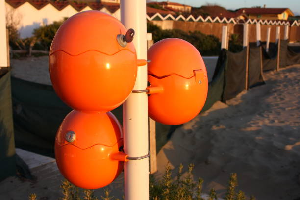 süße orange eier, seltsame und besondere, bizarre ovalen kugeln zum aufladen von handys direkt am meer. akku für smartphone am strand. geniale idee - iphone gratis stock-fotos und bilder