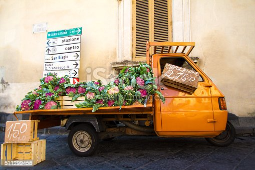 A cute orange vintage truck selling purple cauliflower on a street in Sicily, Italy. Yellow wall and shutters and road signs in the background.