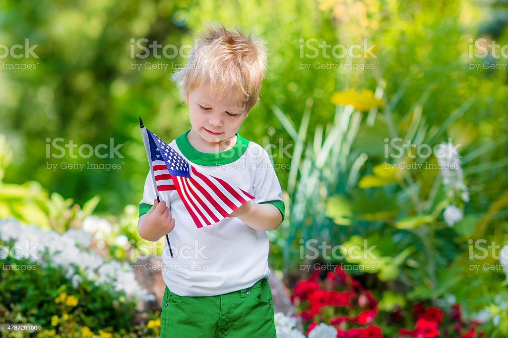 Cute pensive little boy with blond hair holding american flag stock photo