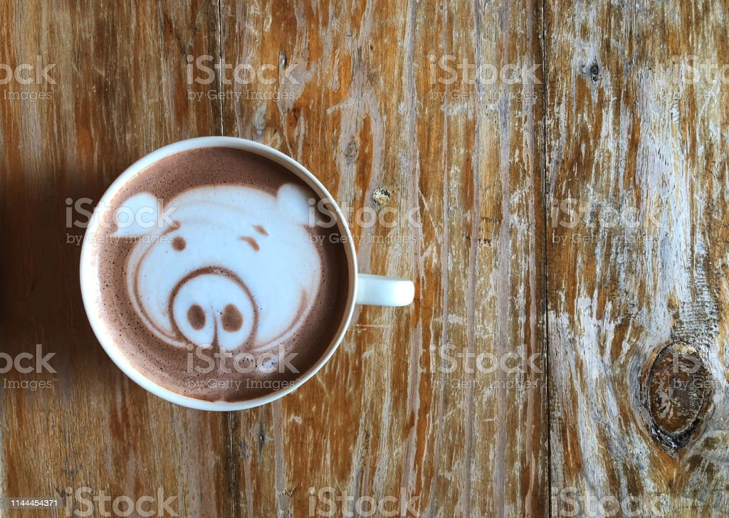 Cute pig face latte art coffee in white cup on wooden table ; cute...